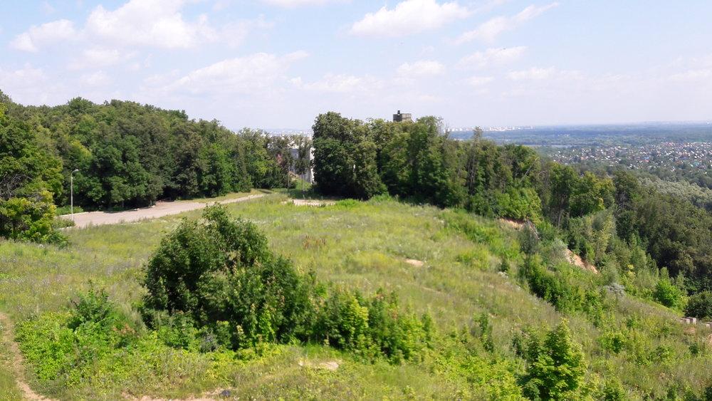 Natomto snímku pořízeném zkabinky lanové dráhy blízko horní stanice jde vidět vrchol starého skokanského můstku a také provozní budovu, ve které mají sportovci zázemí.
