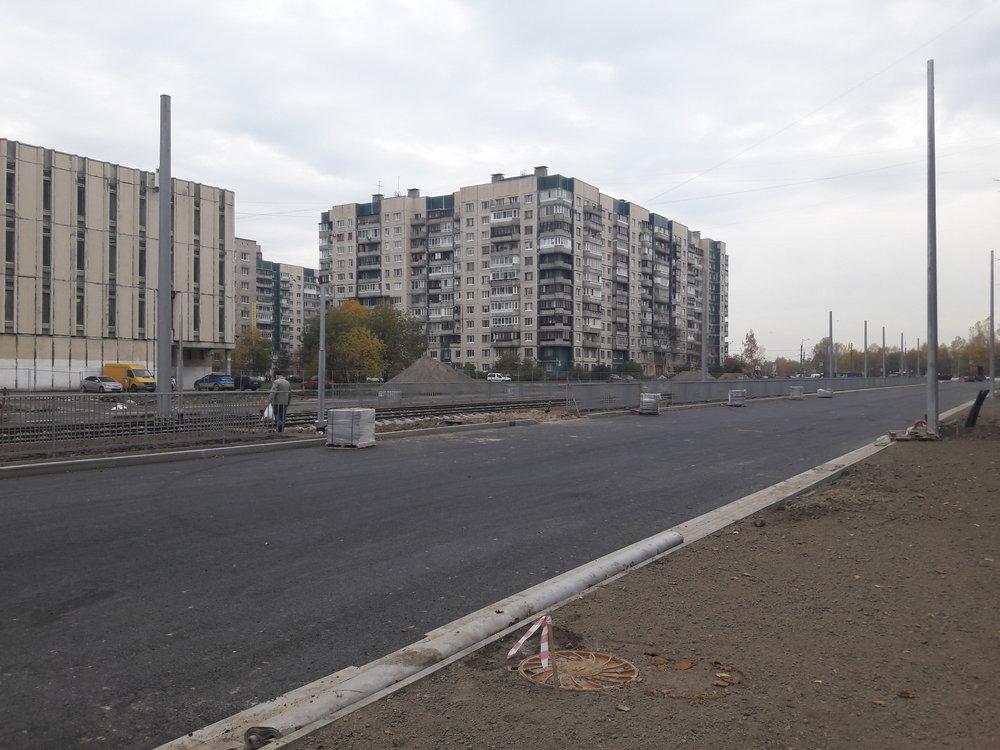 Procházka od Irinovskogo prospekta kprospektu Kosygina po prospektu Nastavnikov. Zde pohled směrem nasever. Tam, kde končí sloupy, jsou položeny dvě výhybky pro obrat  čižiků , kteří sem začnou jezdit ještě vtomto roce. Tramvajová trať, po které jezdí městské tramvaje linek 7 a 10, není nasnímku příliš vidět, je totiž vpozadí, brzy ale začne být také přestavována.