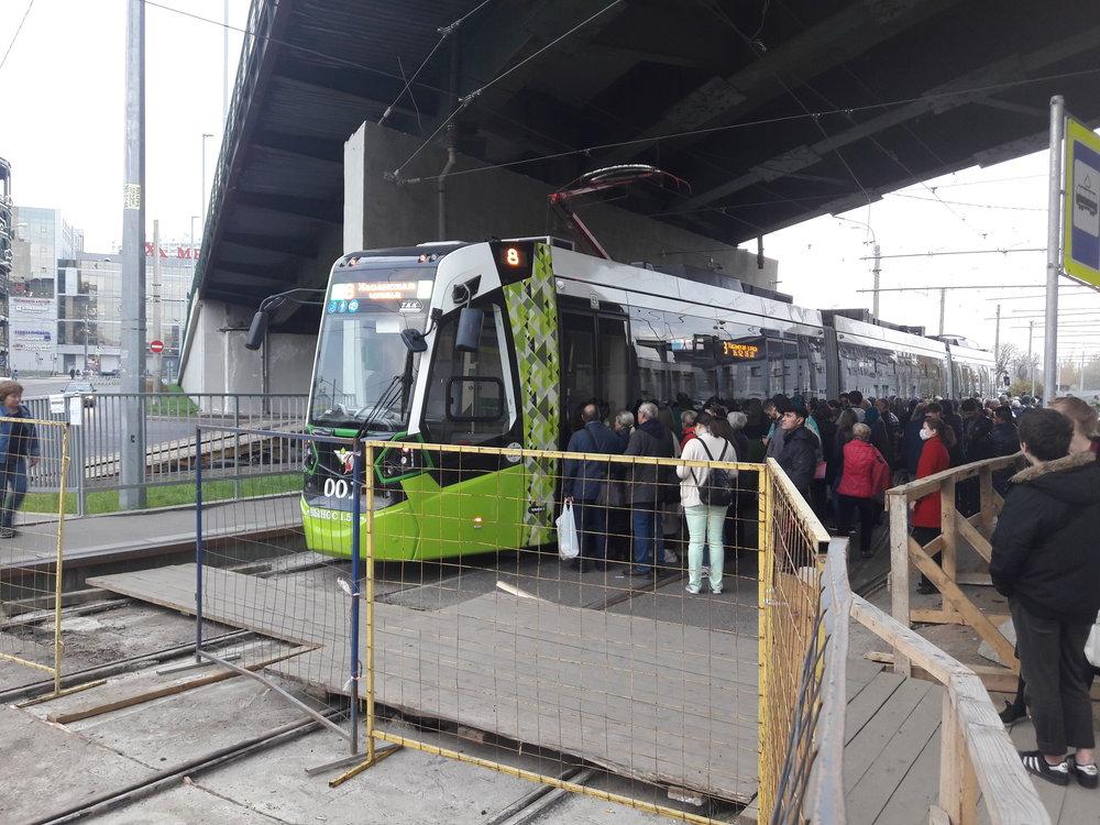 Lidé vystupují jednou stranou, poté přejde řidič do druhé kabiny, a otevře dveře novým cestujícím, kteří čekají nastraně druhé.