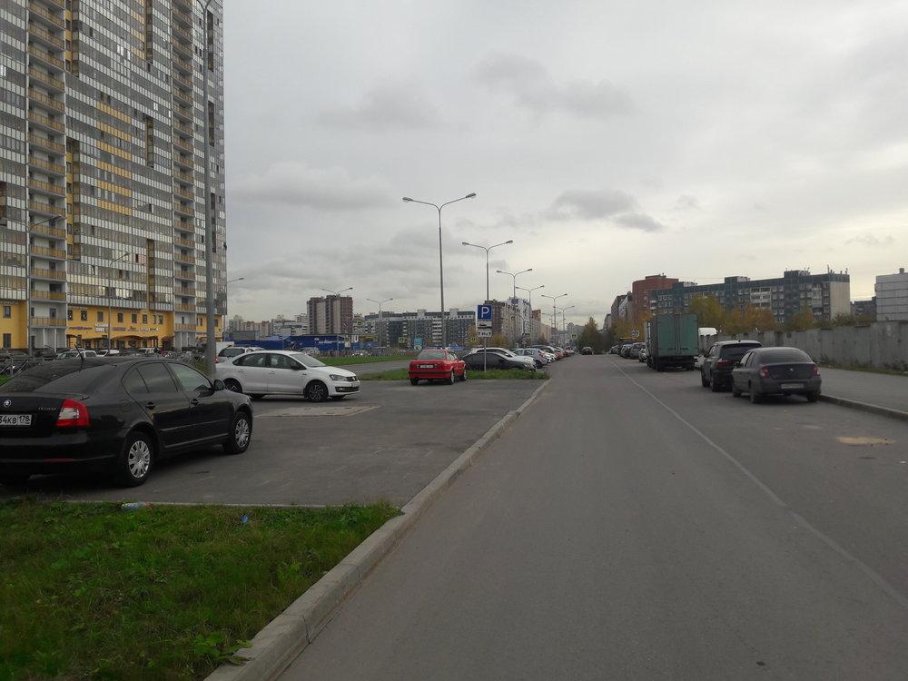 Parašutnaja ulica při pohledu najih. Po ní směřují trolejbusy linky č. 2 kobchodnímu centru, u kterého se otočí, a směřují zpět nasever, akorát již po paralelně vedeném Komendantskom prospektu a už pod dráty.