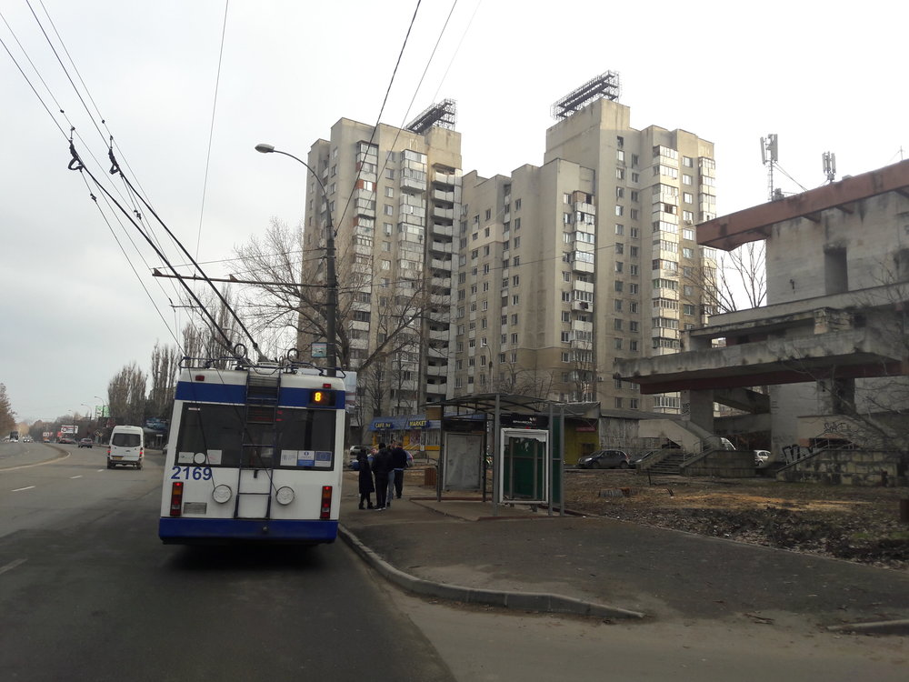 Nástupní (a také občas i výstupní) zastávka konečné Universitatea Agrară naseverozápadě města. Pohled směrem do centra poté, co se trolejbus přes cestu obrátil a projel i smyčkou (viz další obrázek). Podivných objektů, jako je ten vpravo, má Kišiněv docela dost.