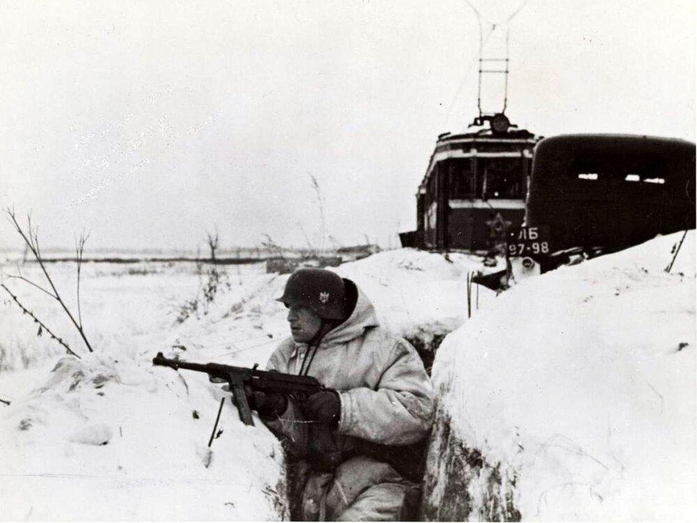 Propagační snímek německé armády zachycující příslušníka Wehrmachtu v zákopu u Leningradu. V pozadí je vidět jednu z leningradských tramvají, která zůstala na území, nad nímž německá vojska získala moc. (zdroj: http://www.gahetna.nl)