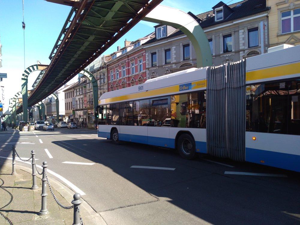 Trolejbus kdysi po příjezdu do Wuppertalu dojel kvýchozí zastávce místní slavné visuté dráhy (za zády fotografa) a vracel se zpět. U visuté dráhy byla trojúhelníková bloková smyčka, nakteré trolejbusy měnily směr. Dne 4. srpna 2014 začaly trolejbusy jezdit kvohwinkelskému nádraží spomocí dieselového pohonu a velká část smyčky, ze které trolejbus právě vyjíždí, tím zůstala nevyužita.