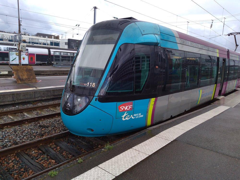 Na snímku z 26. 4. 2019 vidíme vlakotramvaj na nantském hlavním nádraží, kde má pro sebe přizpůsobenu koncovou část jednoho z nástupišť. Přístup k tramvaji je nekrytý, což není za deště zrovna pohodlné řešení.