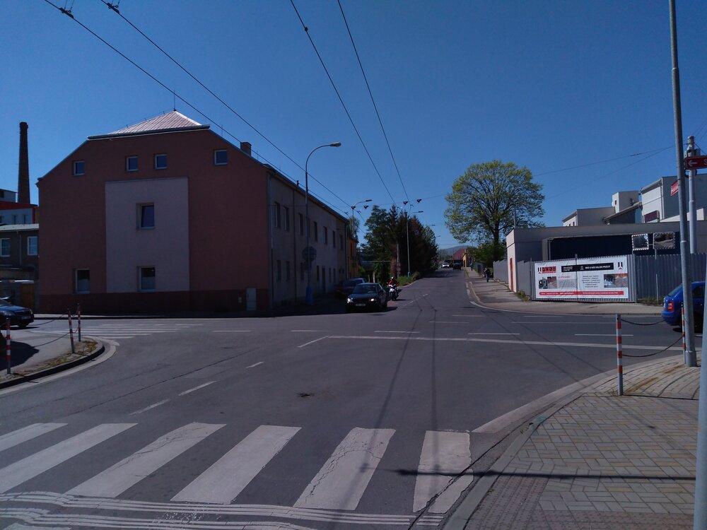 Zde bude začínat trať vedená po ulicích Stanová a Jana Koziny, když bude ztéto křižovatky směřovat vpravo. Pozorní čtenáři jistě uprostřed snímku zaznamenají přístup MHD naprivilegovanou cestu vedenou pod železniční tratí, zatímco okolní doprava využívá úrovňový přejezd. Za železniční tratí je umístěna vozovna trolejbusů, ta ovšem leží napravé straně.
