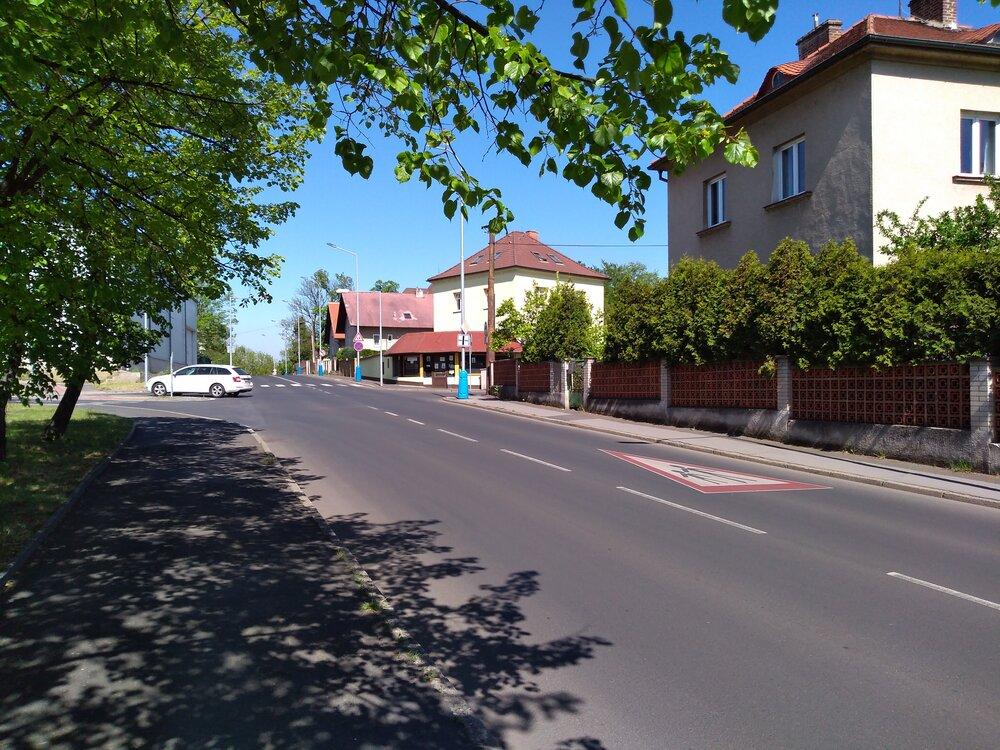 Pohled zulice Bohosudovská ke křižovatce, tentokrát zopačné strany. Tam, kde vidíme bílé auto, budou trolejbusy zatáčet.