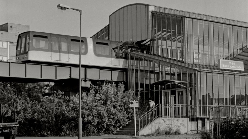 Snímek z 4. 7. 1991, tedy z doby, kdy již berlínské dráze M-Bahn zbývalo jen pár týdnů existence, představuje nejen vzhled vagónu dráhy, ale také moderně pojatých prosklených stanic dráhy. (zdroj: Flickr.com; foto: Petershagen)
